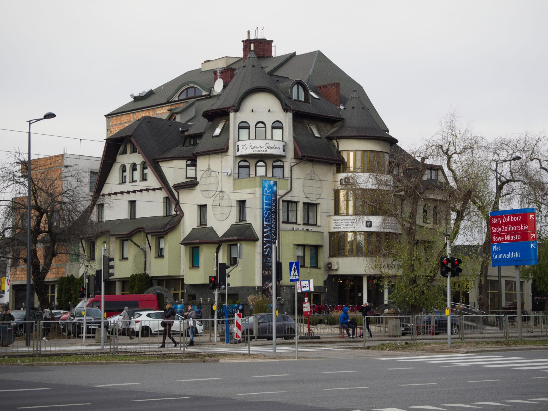 Zdjęcie. Szary, zimowy dzień. W centrum zdjęcia beżowo- zielony budynek z wieloma elementami. Parę kondygnacji.