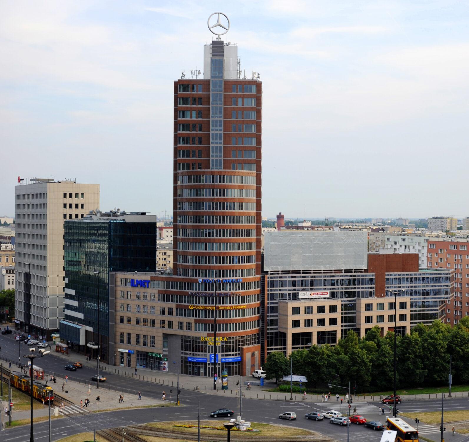 Zdjęcie. Widok miejski. Grupa budynków. Na centralnym planie wysoki, brązowy budynek z logo mercedesa na dachu.